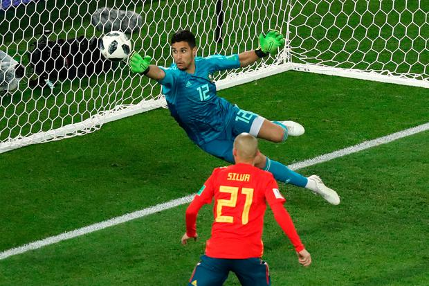 Morocco's Munir Mohamedi dives as a shot from Spain's Gerard Pique (not pictured) goes wide of the post. Photo: REUTERS/Mariana Bazo