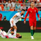 Portugal's Cristiano Ronaldo walks away from Morteza Pouraliganji as his Iranian team-mate Ramin Rezaeian remonstrates with the referee before a red card decision was referred to VAR. Ronaldo, who also missed a penalty escaped with a yellow card and the 1-1 was enough to see Portugal through to face Uruguay. Photo: REUTERS/Murad Sezer