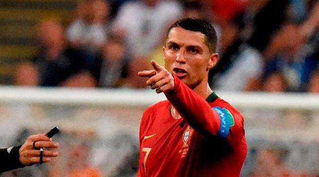 Portugal's forward Cristiano Ronaldo (R) reacts to receiving a yellow card
