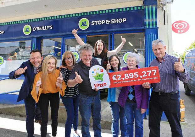Francis O'Reilly, (far right) owner of O'Reilly's XL Store in Swanlinbar in Co. Cavan celebrates with staff and customers after they sold the winning ticket for the €2,895,277 Lotto jackpot on Wednesday June 13th.