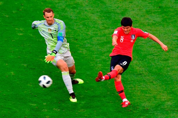 South Korea's midfielder Ju Se-jong (R) passes the ball as he is marked by Germany's goalkeeper Manuel Neuer during the Russia 2018 World Cup Group F football match between South Korea and Germany at the Kazan Arena in Kazan on June 27, 2018. / AFP PHOTO / Luis Acosta