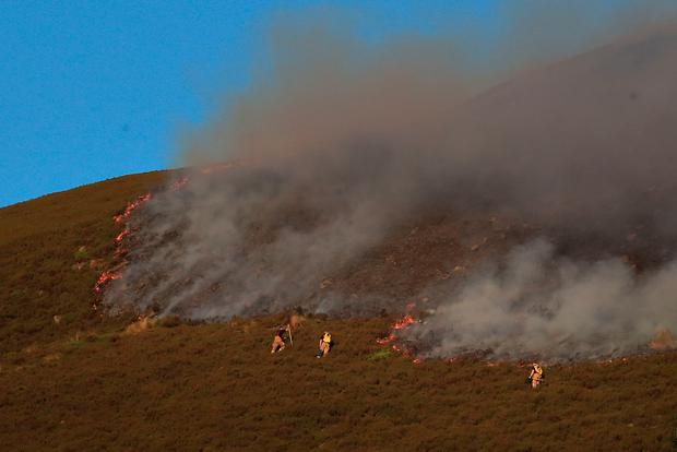 Firefighters tackle the wildfire on Saddleworth Moor which continues to spread after the blaze was declared a major incident by Greater Manchester Police. Peter Byrne/PA Wire