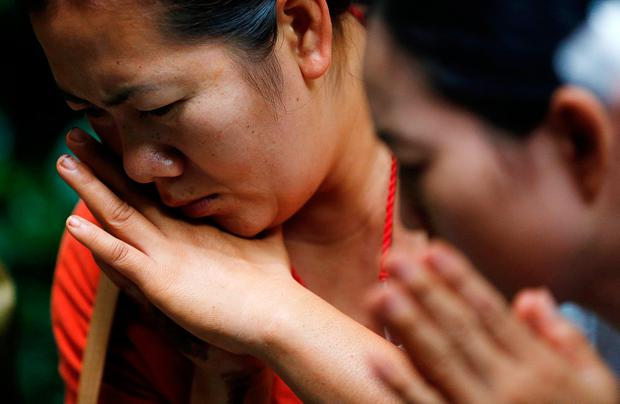Family members pray near the Tham Luang cave complex during a search for members of an under-16 soccer team and their coach, in the northern province of Chiang Rai, Thailand, June 27, 2018. REUTERS/Soe Zeya Tun