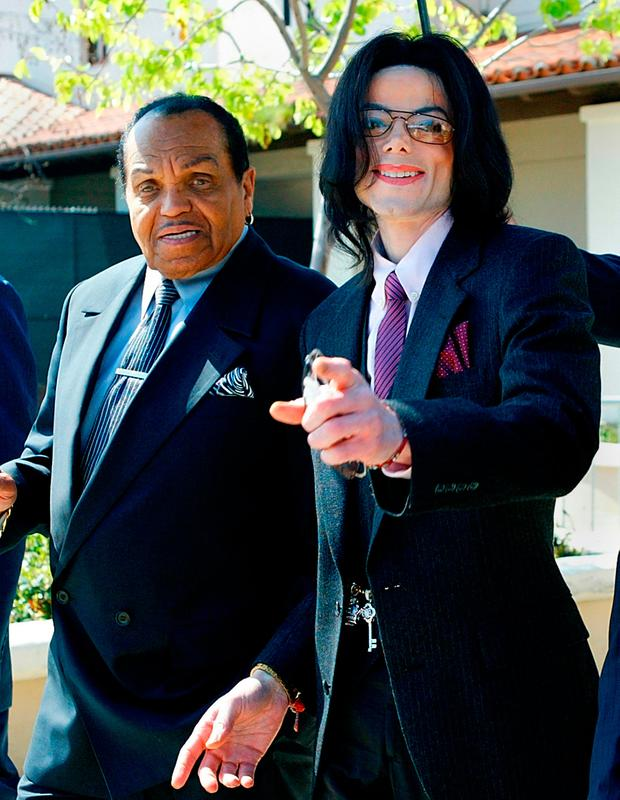 (FILES) In this file photo taken on March 8, 2005 singer Michael Jackson (R) gestures as he and his father, Joseph Jackson, depart the Santa Maria Superior Court