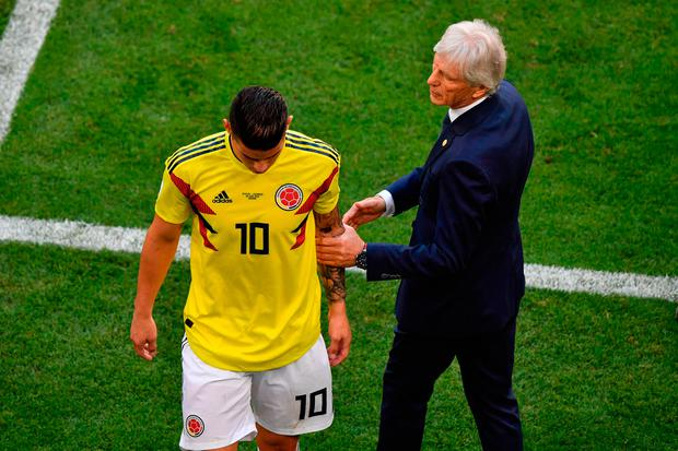 James Rodriguez leaves the football pitch due to an injury as he is comforted by Colombia coach Jose Pekerman (R). Photo: AFP/Getty Images