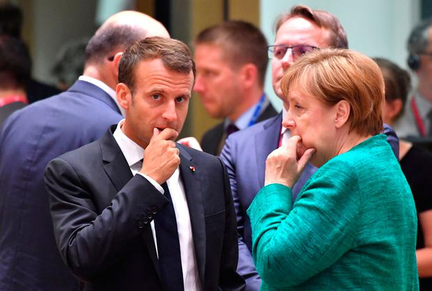 German Chancellor Angela Merkel speaks to French President Emmanuel Macron during the EU summit in Brussels. Photo: AP
