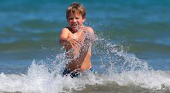Cillian McGee (11) from Castleknock plays in the water at Portmarnock beach. Photo: Damien Eagers