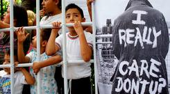 Children perform inside a simulated cage beside a placard in reference to US first lady Melania Trump during a protest against US immigration policies outside the US embassy in Mexico City, Mexico. Photo: Reuters