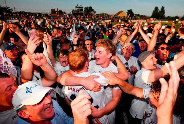 Kildare players Daniel Flynn and Keith Cribbin celebrate last night's victory over Mayo in Newbridge as supporters crowd around them. Photo: Stephen McCarthy