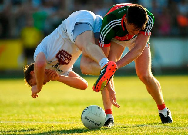 Paul Cribbin of Kildare is tackled by Diarmuid O'Connor of Mayo. Photo: Piaras Ó Mídheach/Sportsfile