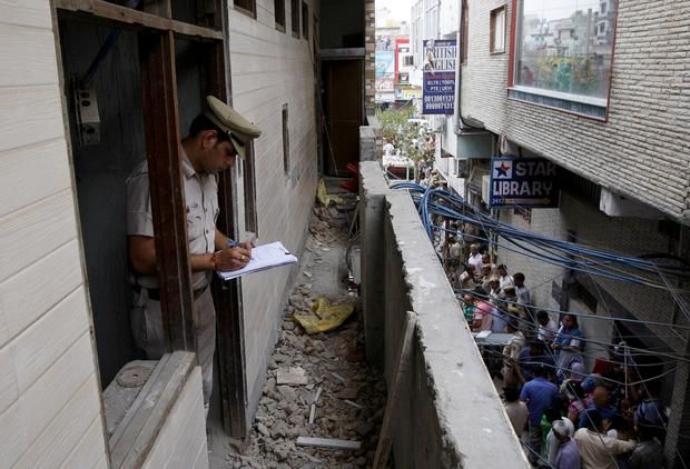 A policeman writes notes in the house where the bodies of eleven members of a family were found dead in Burari, in New Delhi, India, July 1, 2018. REUTERS/Stringer