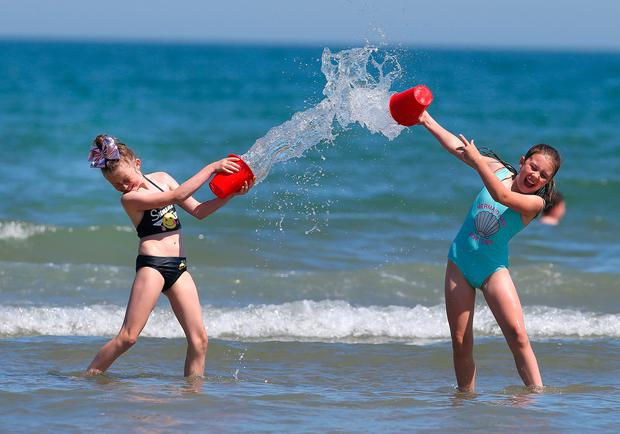 Robin Larkin, 9, left and Lucy Shields, 10, from Donnycarney play in the water at portmarnock beach. Picture credit; Damien Eagers