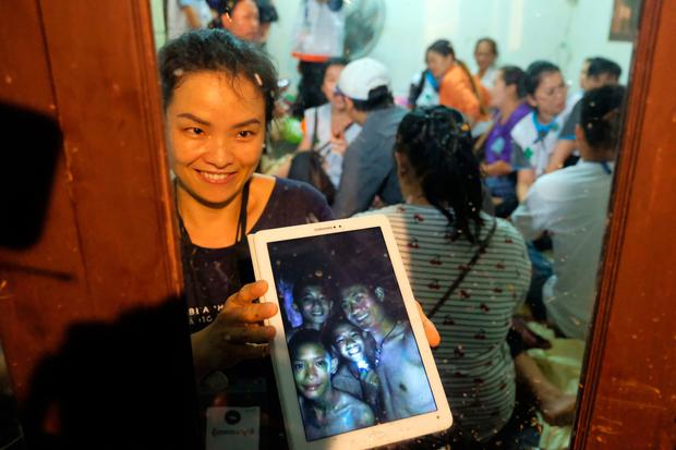 Relatives of the missing boys show photos of them after the 12 boys and their soccer coach have been found alive in the cave where they've been missing for over a week (Photo by Linh Pham/Getty Images)