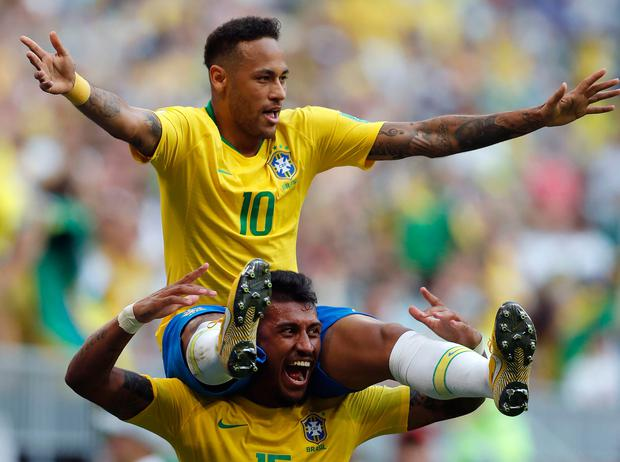 Brazil's Neymar, top, celebrates with team mate Paulinho