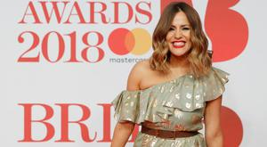 British television presenter Caroline Flack poses on the red carpet on arrival for the BRIT Awards 2018 in London on February 21, 2018. / AFP PHOTO / Tolga AKMEN