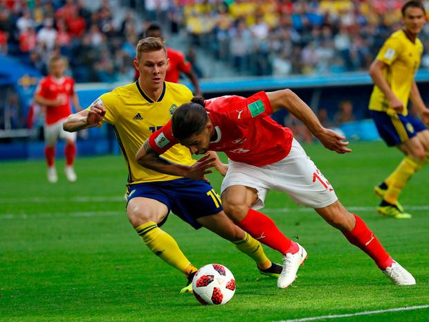 Switzerland's Ricardo Rodriguez, right, vies for the ball with Sweden's Emil Krafth. Photo: Darko Bandic/AP Photo