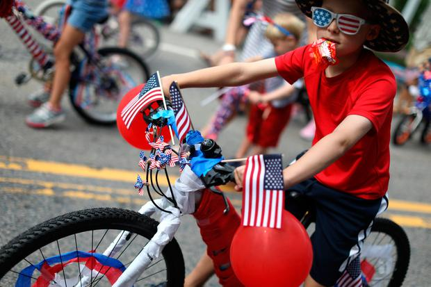 A boy rides a decorated bicycle down Main Street during the annual Fourth of July parade in Barnstable Village on Cape Cod, Massachusetts, U.S. REUTERS/Mike Segar