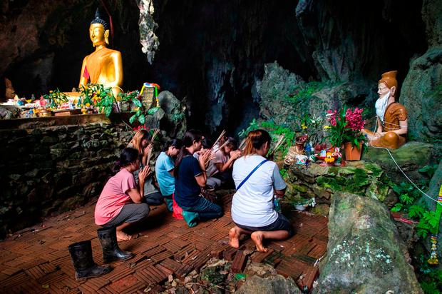 Family members of the 12 boys and their football coach trapped by floods in the Tham Luang cave pray at a nearby shrine as operations continue to rescue them. Photo: AFP/Getty Images