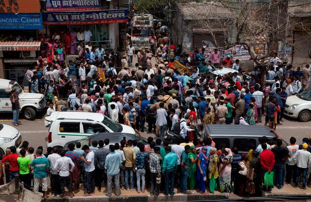 Pedestrians gather near the house where Indian police found 11 bodies in Burari village, north Delhi, India. Photo: AP