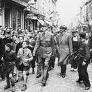 Lead by excited children, General Charles de Gaulle walks through the streets of Paris after France's liberation from Nazi Germany in 1944