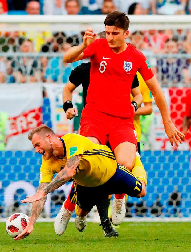 England defender Harry Maguire battles with Sweden's John Guidetti in yesterday's World Cup quarter-final. Photo:Carlos Garcia Rawlins/Reuters