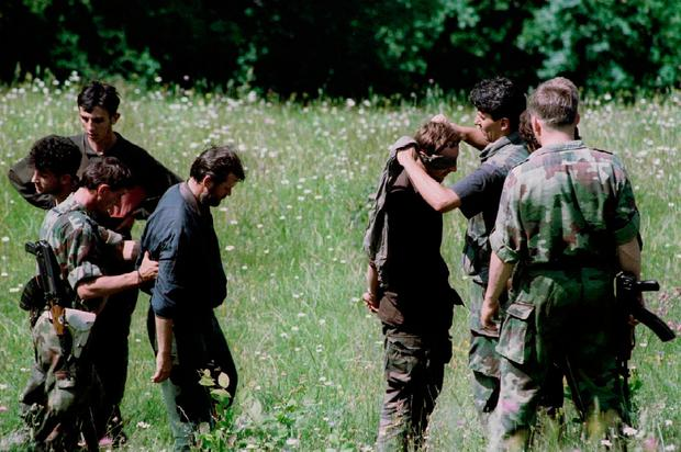 A Bosnian Croat soldier blindfolds Muslim prisoners before turning them over to Bosnian Serb forces for 'interrogation' in Konjic, Bosnia on June 14, 1993