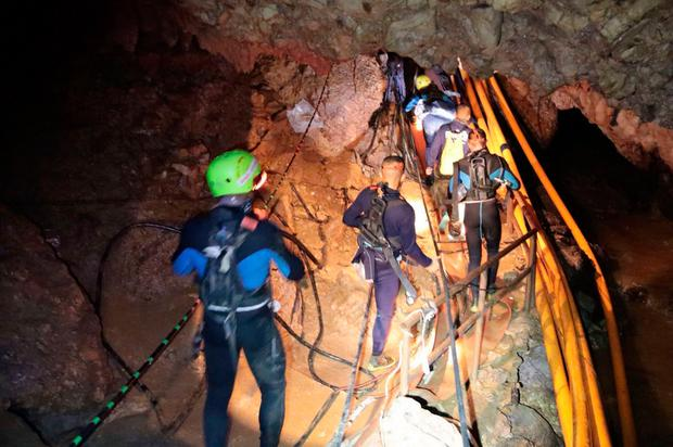 Thai rescue team members walk inside a cave where 12 boys and their soccer coach have been trapped since June 23 (Royal Thai Navy via AP)