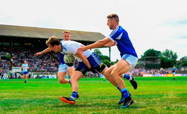 Jack McCarron of Monaghan in action against Colm Begley of Laois. Photo by Ramsey Cardy/Sportsfile