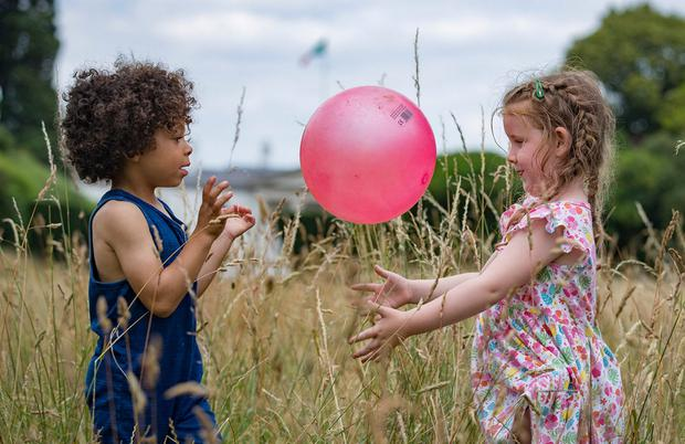 Kyron Burke (4) and Lucia O'Brien (4), from Bray, play in the sun. Photo: Arthur Carron