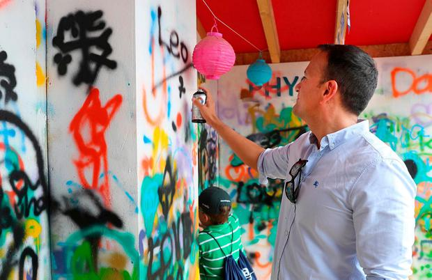 "Taoiseach Leo Varadkar writes ""Leo"" at a graffiti wall at the Laya Healthcare City Spectacular in Dublin's Merrion Square yesterday. Photo: Marc O'Sullivan"
