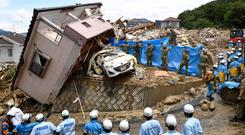 Rescue workers look for missing people in Kumano town. Kyodo/via REUTERS
