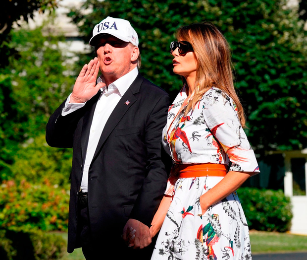 US President Donald Trump talks to reporters as he walks with first lady Melania Trump at the White House. Photo: Reuters