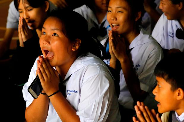 Classmates of the trapped boys at Mae Sai Prasitsart school, close to the caves, pray after their teacher announced that more of the footballers had been rescued. Photo: REUTERS