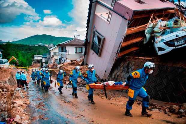 Police arrive to clear debris scattered on a street in a flood-hit area in Kumano, Hiroshima prefecture. Photo: AFP/Getty Images*