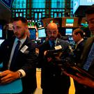 Traders work on the floor at the opening bell of the Dow Industrial Average at the New York Stock Exchange