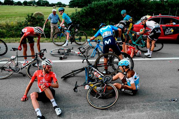 GROUNDED: France's Axel Domont (right) and Poland's Tomasz Marczynski (left) on the road after being caught in a massive pack fall during yesterday's fourth stage of the Tour de France. Pic: Getty Images