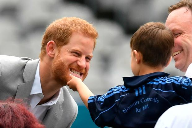 The Duke of Sussex has his beard stroked by a small child in Croke Park on the second day of his visit to Dublin, Ireland. Dominic Lipinski/PA Wire