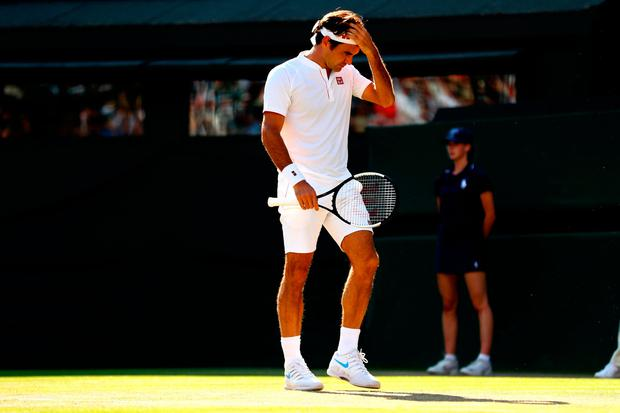 LONDON, ENGLAND - JULY 11: Roger Federer of Switzerland wipes his forehead against Kevin Anderson of South Africa during their Men's Singles Quarter-Finals match on day nine of the Wimbledon Lawn Tennis Championships at All England Lawn Tennis and Croquet Club on July 11, 2018 in London, England. (Photo by Michael Steele/Getty Images)