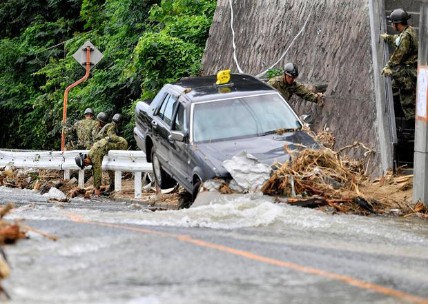 Japan Ground Self-Defense Force members search around a damaged taxi on a street flooded by torrential rain in Hiroshima. Kyodo/via REUTERS