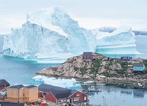 A huge iceberg towers over houses and buildings after grounding near the village of Innarsuit, a settlement in north-west Greenland. Photo: Getty