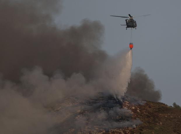Air Corps Helicopter drops sea water on to a gorse fire on Bray head this evening after people flying drones had halted their efforts