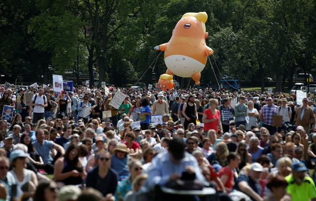 A blimp resembling U.S. President Donald Trump floats above demonstrators marching to protest against the visit of Trump, in Edinburgh, Scotland: Reuters/Andrew Yates