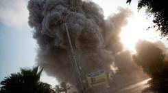 Smoke raises in the background following an Israeli airstrike hits a governmental building in Gaza City , Saturday, July 14, 2018. The Israeli military carried out its largest daytime airstrike campaign in Gaza since the 2014 war as Hamas militants fired dozens of rockets into Israel, threatening to spark a wider conflagration after weeks of tensions along the volatile border. No casualties or major damage was reported on either side, and Israel said it was focused on hitting military targets and was warning Gaza civilians to keep their distance from certain sites.(AP Photo/Khalil Hamra)
