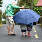 Aoibhinn O'Hanlon (5) and her brother Ronan (2) take a walk in the rain in Castlegregory Co Kerry as dad Eoin O'Hanlon holds a giant umbrella over the kids too keep them dry . Photo By Domnick Walsh © Eye Focus LTD