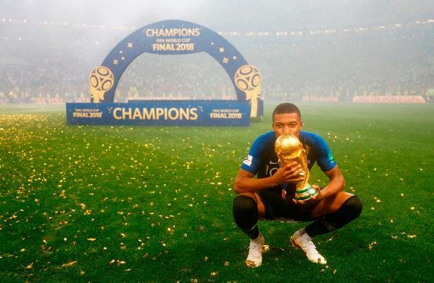 France's Kylian Mbappe celebrates with the trophy after winning the World Cup. Photo: Kai Pfaffenbach/Reuters