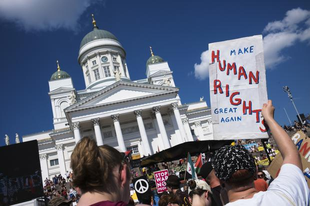 A rally against US president Donald Trump in Helsinki (AP)