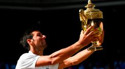 Novak Djokovic celebrates with the trophy after winning the men's singles final against South Africa's Kevin Anderson. Photo: Tony O'Brien/Reuters