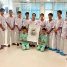 The 12 boys and their coach pose with a sketch of the diver who died trying to rescue them. Photo: AP