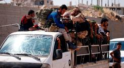 Syrian rebels ride on a truck during evacuation from Daraa city yesterday as Syrian government forces heavily bombed the neighbouring province of Quneitra making a ground advance in the zone. Photo: Reuters