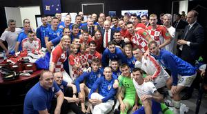 Russian President Vladimir Putin and Croatian President Kolinda Grabar-Kitarovic pose for a picture with team members as they visit the dressing room of team Croatia after the match.
